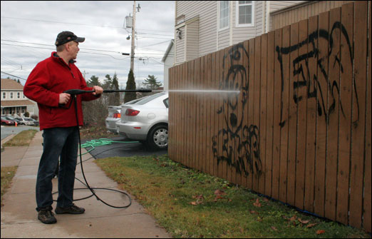 Oceanview Drive resident Dave Buffett attempts to clean graffiti off his fence using a high-pressure water hose. Police are actively investigating incidents of graffiti along Oceanview Drive.